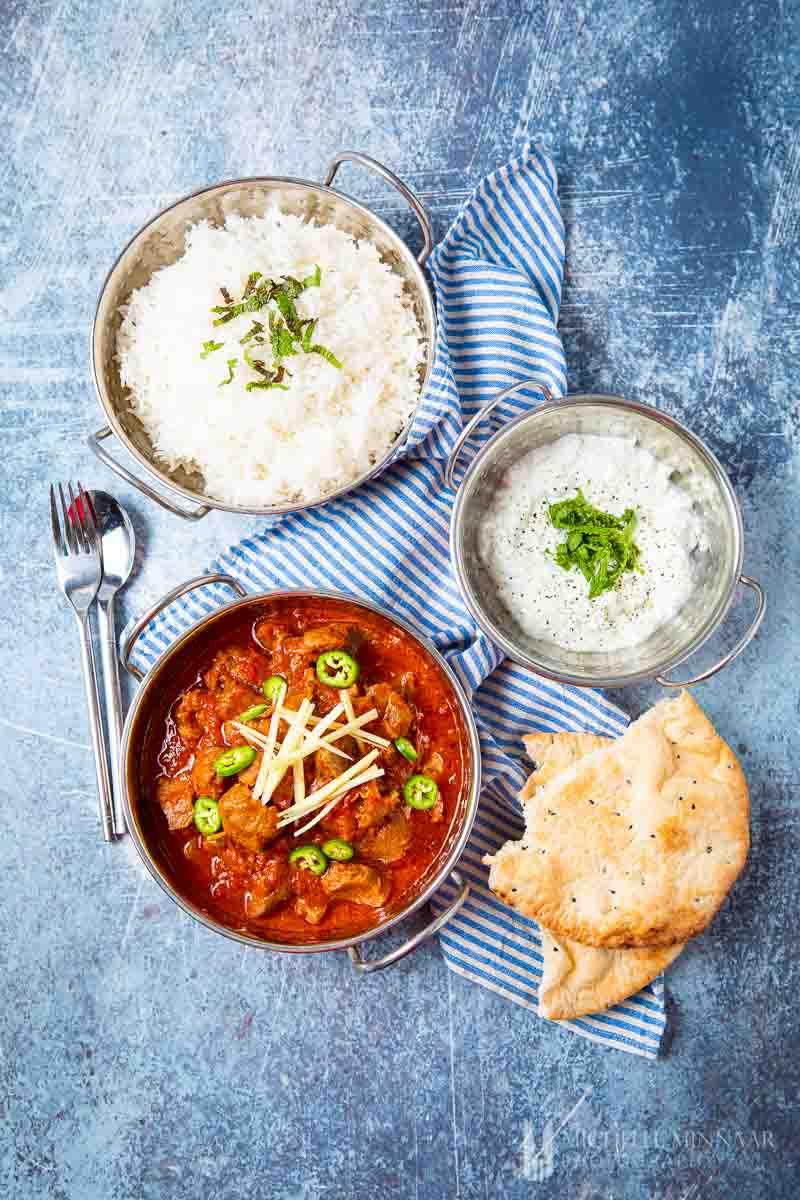 Bowl of lamb karahi , white sauce, white sauce and pita bread