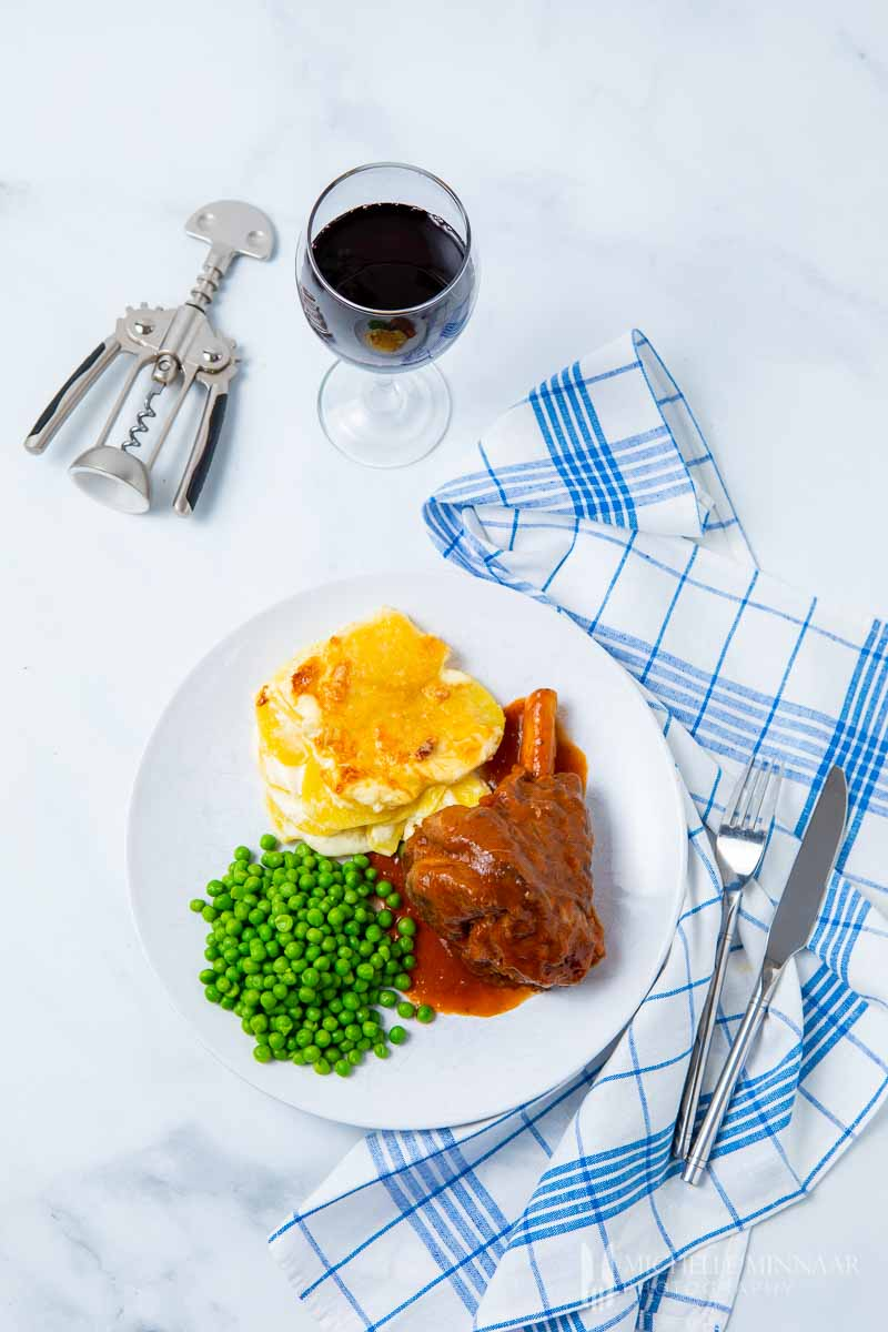 A plate of slow cooker lamb shanks, peas and potatoes