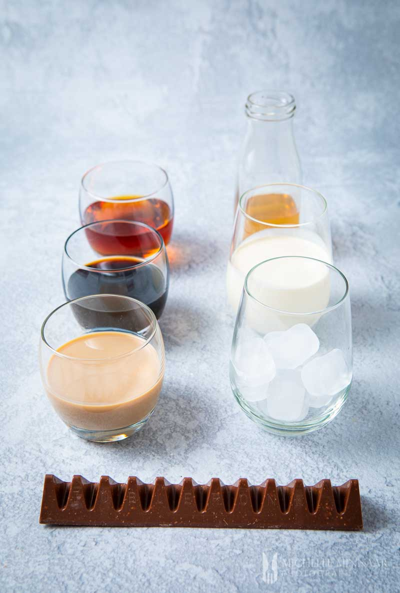 Glasses of liquid ingredients to make a Toblerone cocktail