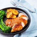 Plate of Chicken with Rhubarb Sauce and a side of potatoes and broccolini