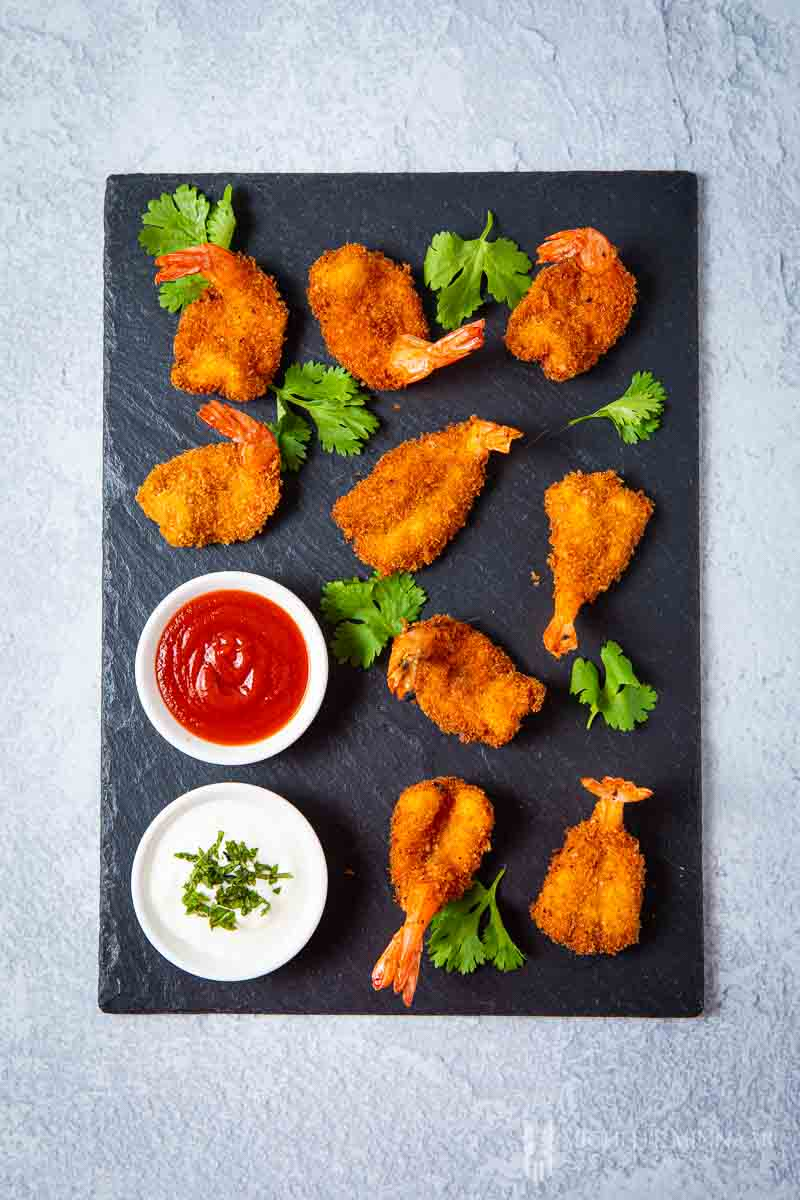 king prawn butterfly on a black board with dipping sauce