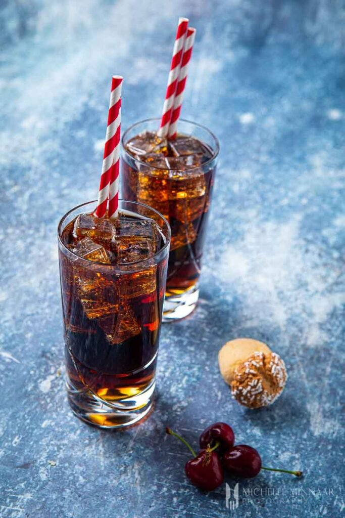 Two clear glasses of amaretto and coke