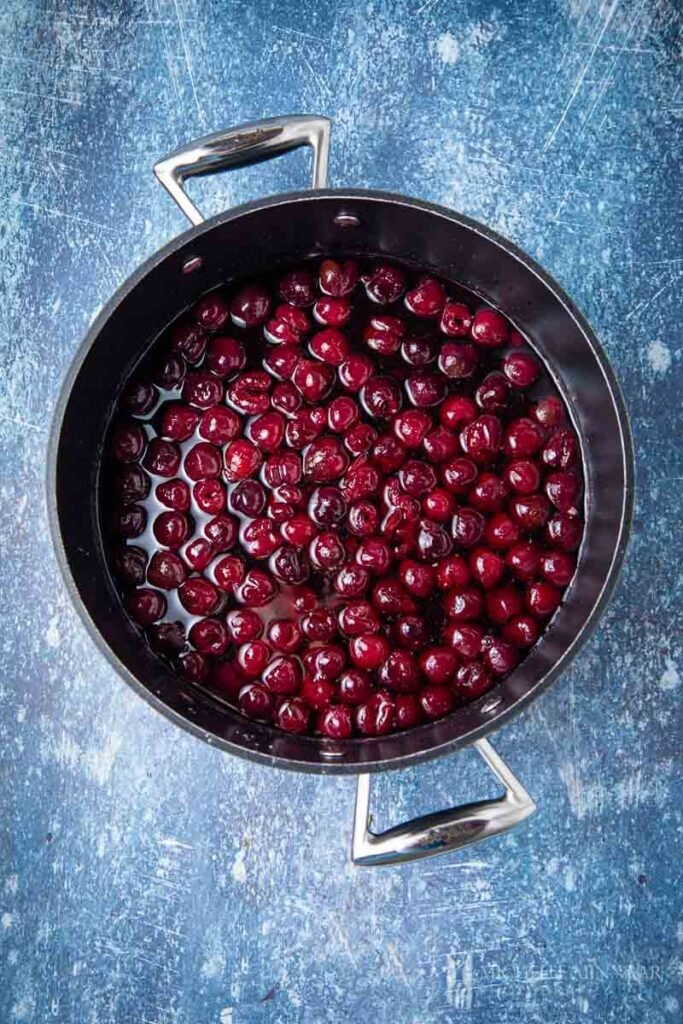 Red cherries simmering in a pot