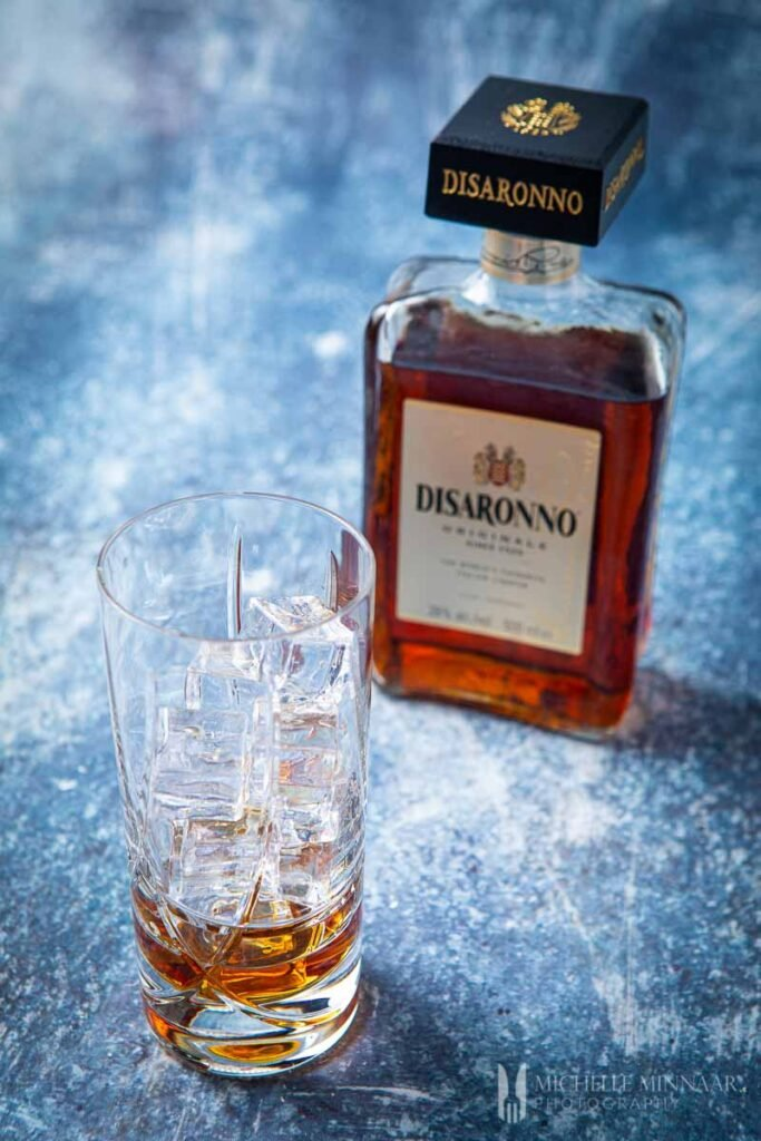 Empty glass with ice and a bottle of amaretto