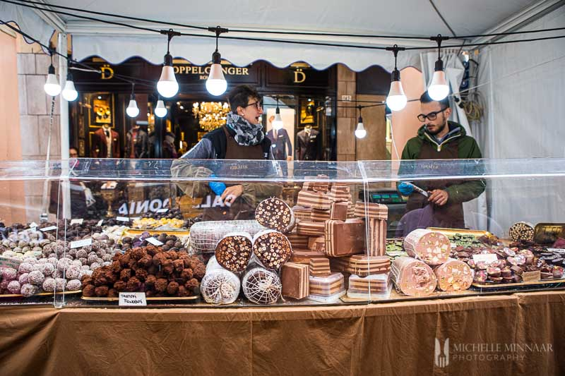 Chocolate salami displayed at chocolate stall with two attendants.