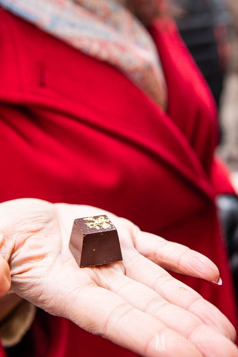 A lady in a red coat, holding a balsamic vinegar chocolate.