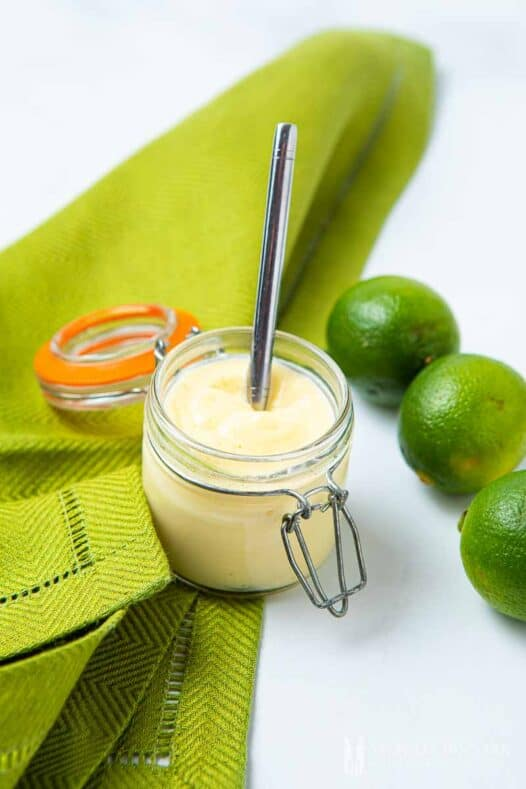 Jar of creamy lime curd with fresh limes