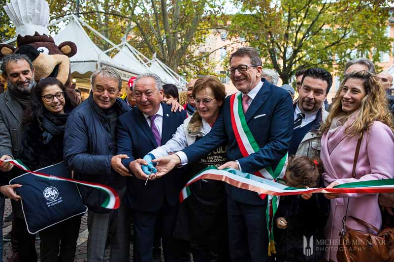 Modena's mayor cutting Sciocola's ribbon with other notable figures.