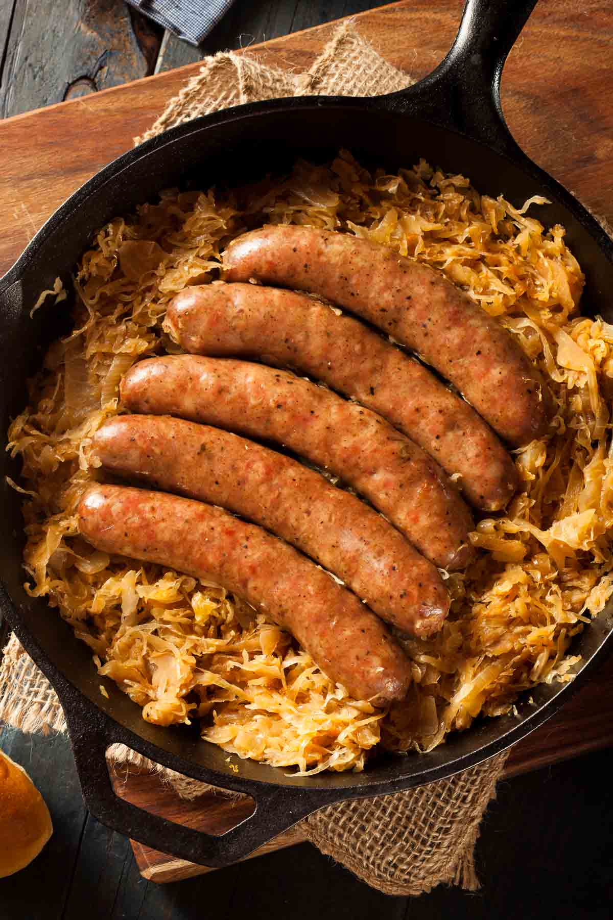 Browned German sausage over a layer of sauerkraut in a skillet