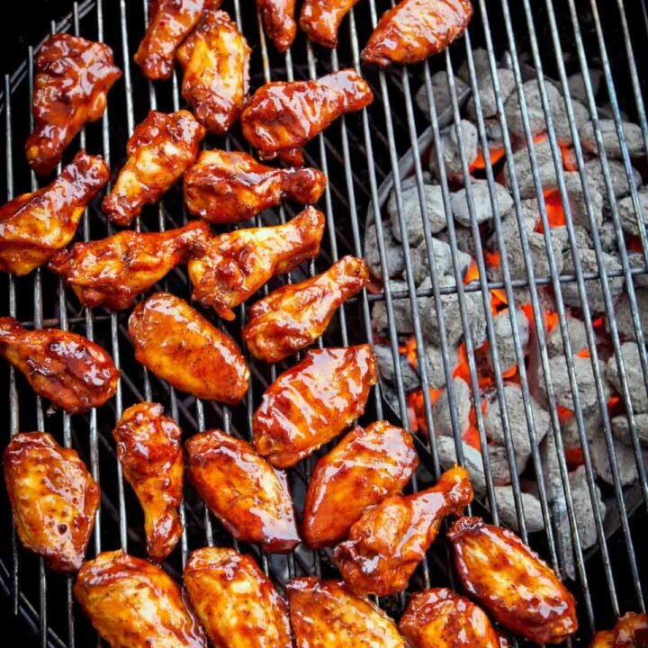 Chicken wings smothered in sauce on a bbq grill