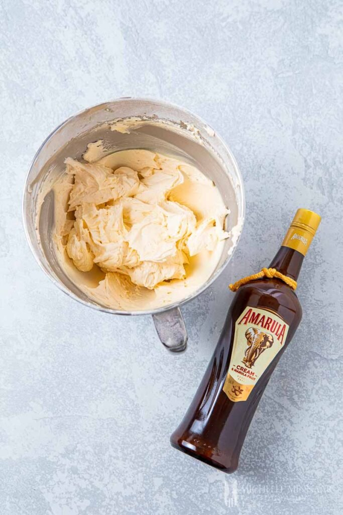 Bowl of buttercream and a bottle of Amarula