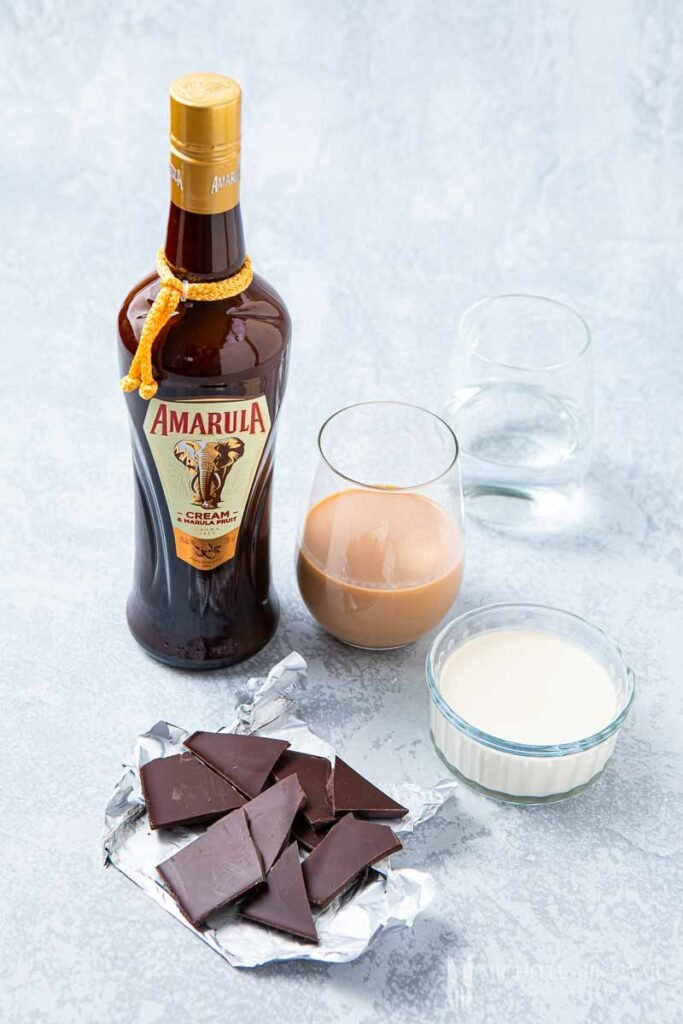 Bottle of Amarula, glass of tan liquid and chunks of chocolate