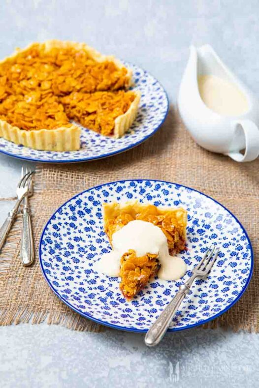 Whole cornflake tart with a slice removed and a dollap of creme on top