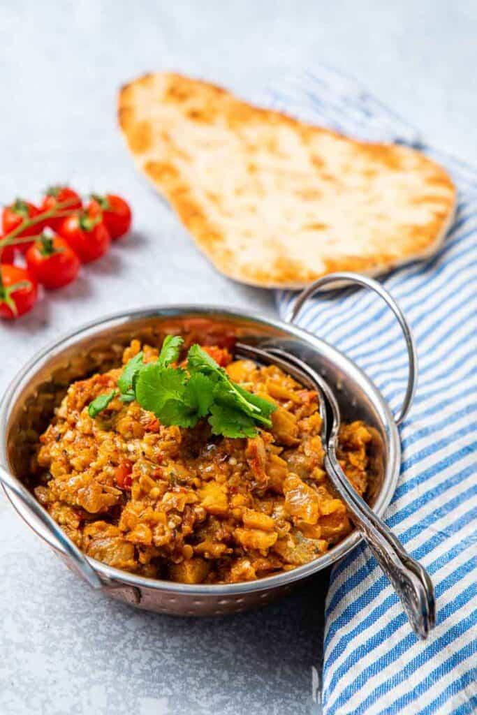 Bowl of brinjal bhaji and naan bread