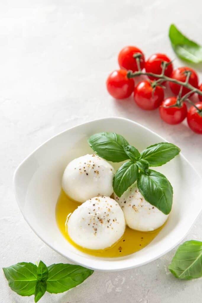 Balls of fresh mozzarella cheese in oil and basil