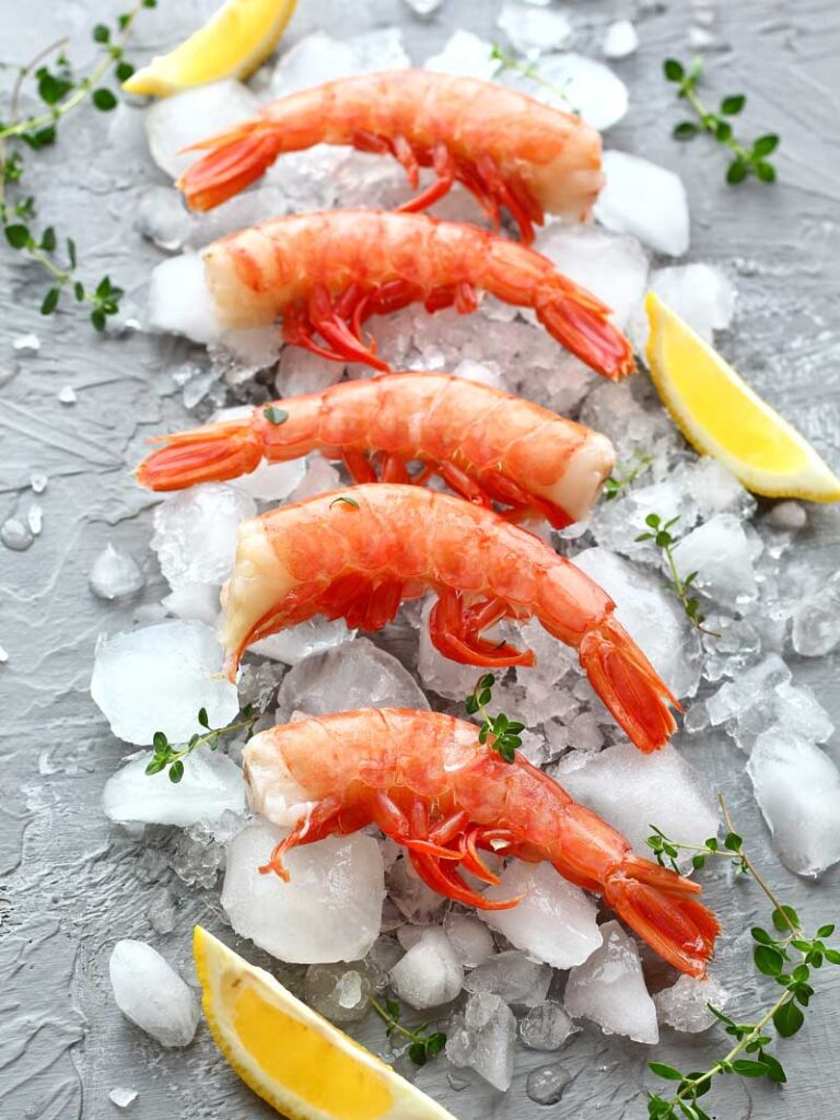 Red prawns on ice with lemon wedges