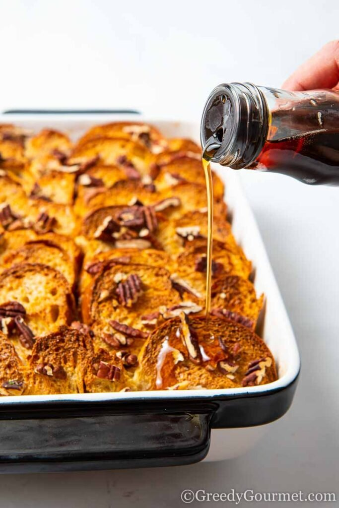 Syrup being poured onto a baked French toast casserole