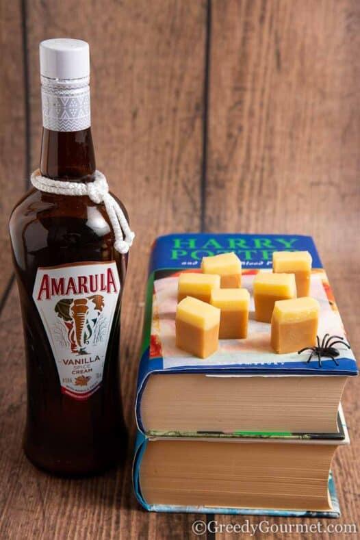 Bottle of Amarula and chunks of alcoholic fudge on Happy Potter books
