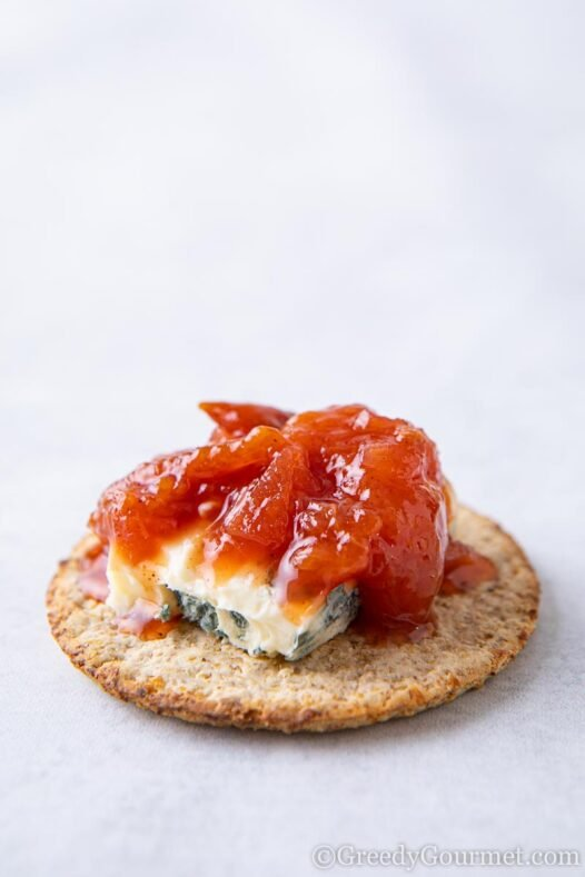 Cracker topped with blue cheese and a spiced plum chutney