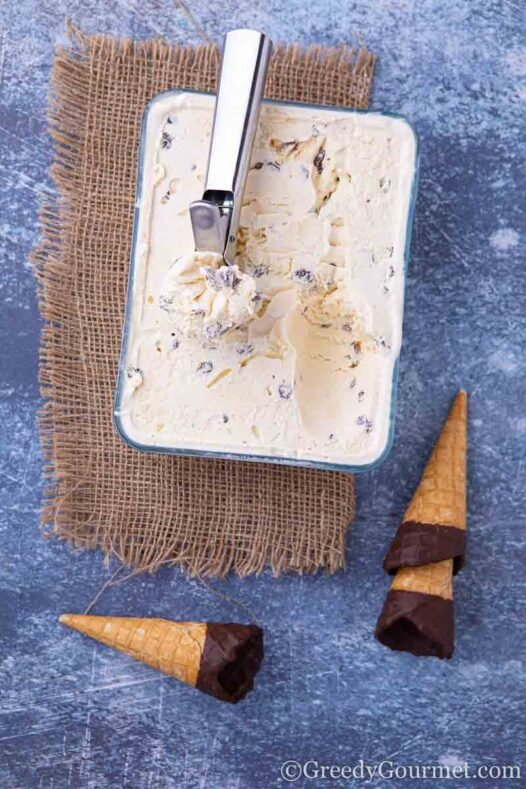 Fresh raisin ice cream in a glass container and ice cream cones