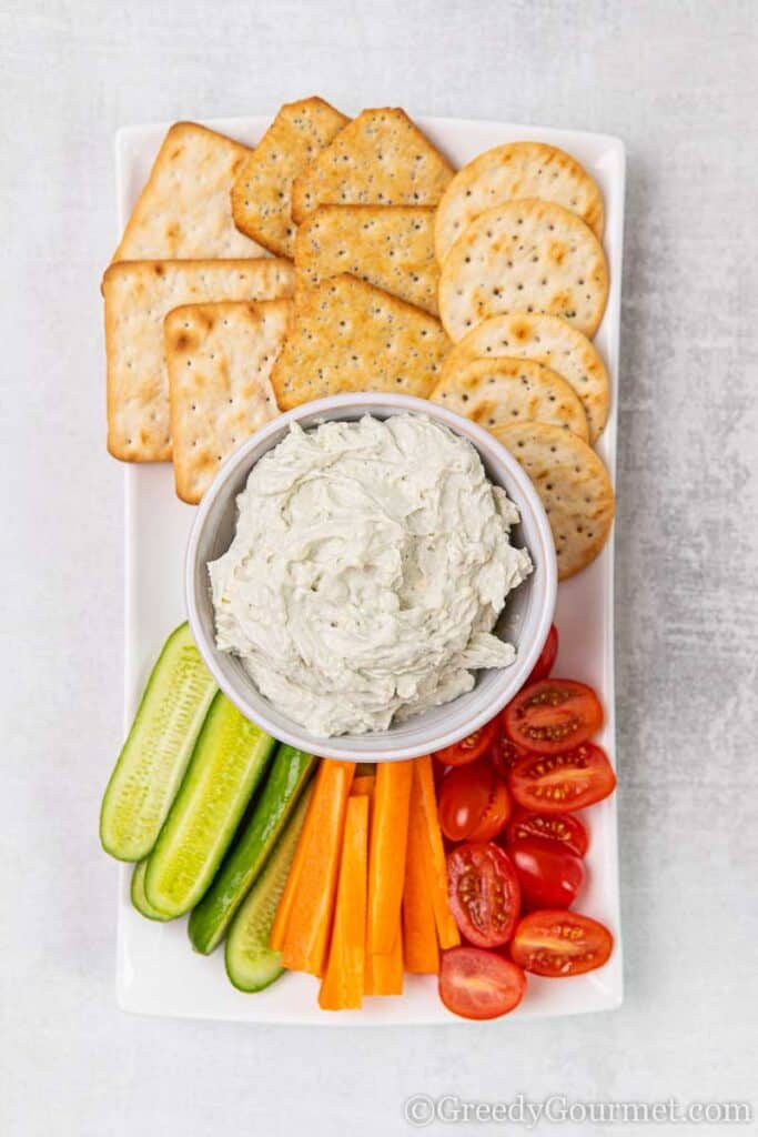 Bowl of white vegetarian dip recipe and crackers with vegetables