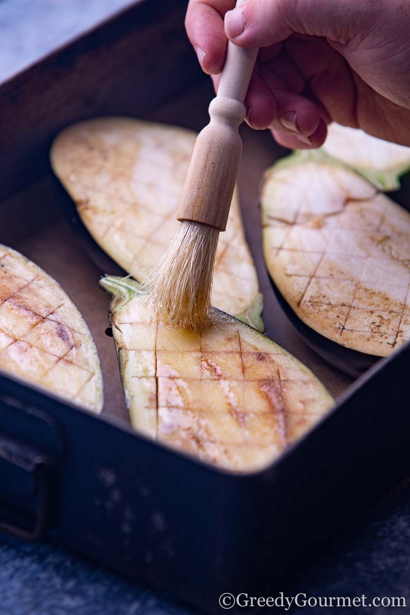 Oil being brushed onto eggplant