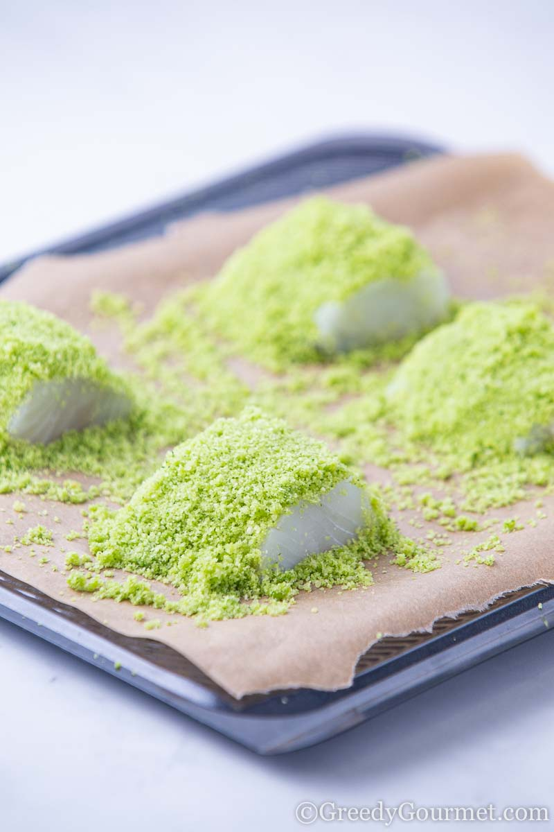 Raw cod dusted with green crust ready to bake