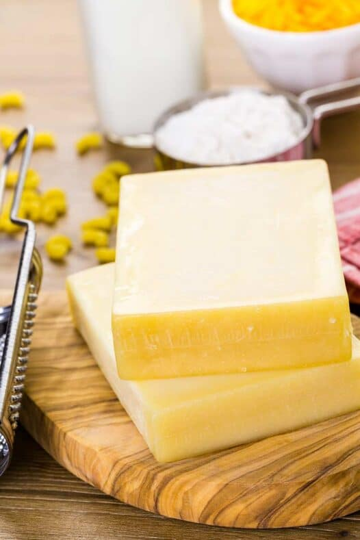 Stacked gruyere cheese on a cutting board