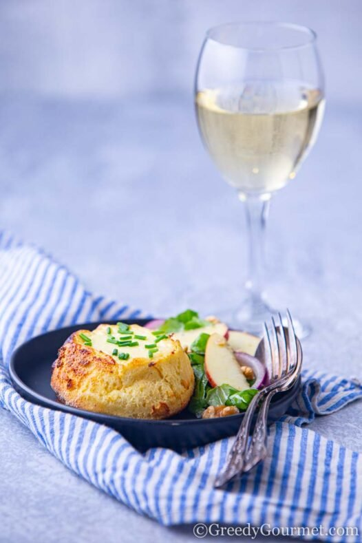 A plate of souffle recipe and a glass of white wine