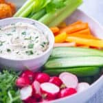 Bowl of white creamy vegan ranch dressing and fresh cut vegetables