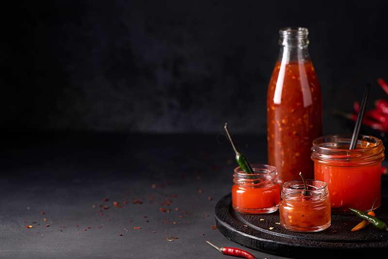 Four different size jars full of Sriracha