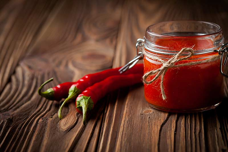 Two red peppers and one jar of Sriracha